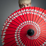 Girl Peeking Over Red Parasol Royalty Free Stock Photos