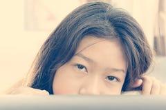 Girl peeking from of pillows on sofa. Cute asian girl peeking from of pillows on sofa royalty free stock photo