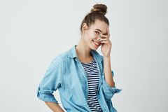 Girl peeking to see surprise. Cute and lovely european girl with bun hairstyle in denim shirt holding fingers over face. While smiling, standing half-turned royalty free stock images