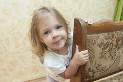 Girl peeks out from behind the chair Royalty Free Stock Image