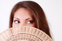 girl peeks out from behind fan Stock Photo