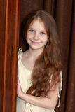 The girl peeks out from behind the wardrobe. Gentle little girl with long brown hair to her waist . The girl peeks out from behind old closet royalty free stock photography