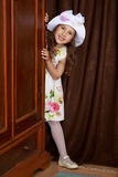 The girl peeks out from behind the wardrobe. Gentle little girl in a white dress with roses and a white hat peeks out from behind an old oak wardrobe. Retro Stock Image