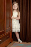 The girl peeks out from behind the wardrobe. Lovely little round-faced girl with long, blonde hair below the shoulders, in a white dress. The girl peeks out from Royalty Free Stock Photos