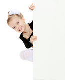 The girl peeks out from behind white banner. Royalty Free Stock Photos