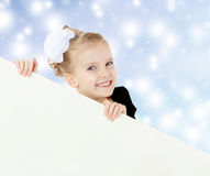 The girl peeks out from behind white banner. Royalty Free Stock Image