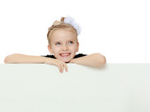 The girl peeks out from behind white banner. Stock Image