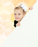 The girl peeks out from behind white banner. Stock Photos