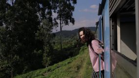 The girl peeks out of the train on the way.  stock footage