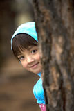 Girl peeks from tree. Royalty Free Stock Images