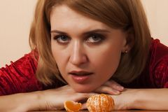 Girl with peeled mandarin Royalty Free Stock Photos