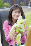 Girl peeling husk off corn cob Stock Images