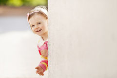 Girl peeping from behind the wall Stock Images