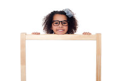Girl peeping from behind white writing board. Cute girl kid with eyeglasses peeping from behind blank whiteboard royalty free stock images