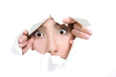 Girl peeping through hole in white paper Royalty Free Stock Images