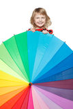 Girl peeping out from behind the colorful umbrella. Little girl hiding behind a colorful umbrella royalty free stock photography