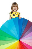 Girl peeping out from behind the colorful umbrella. Little girl hiding behind a colorful umbrella stock photo