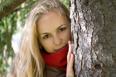 Girl Peeping out through Tree Stock Photos