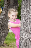 Girl peeping out through tree. Portrait young girl peeping out tree, in summer park Royalty Free Stock Images