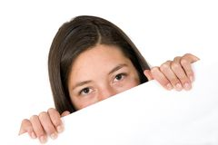 Girl peeping over a white card Stock Photo