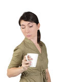 Girl peeps into a cup with one eye closed Royalty Free Stock Photography