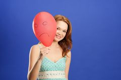 Girl peering over red angry balloon Royalty Free Stock Image