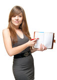 Girl with a pen and open on a blank page datebook. A pretty young woman in a grey dress sweetly smiles and indicates a ballpoint pen on the blank page of the Royalty Free Stock Image