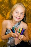 Girl with pencil. Long-haired girl with a pencil in her hands Royalty Free Stock Photos