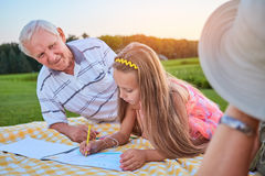 Girl with pencil drawing outdoors. Grandpa looking at granddaughter Royalty Free Stock Images
