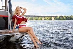 Beautiful girl siting on the edge of yacht stock photos