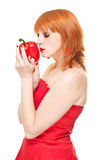 Girl with pepper in red dress isolated. Portrait of young attractive redhead woman in red dress holding fresh red pepper, isolated on white background Stock Image