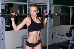 Girl with perfect body performing barbell exercise Stock Photos