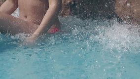Girl with perfect body sits under waterfall slow motion. Girl with perfect body sits in clear pool under artificial waterfall among splashing drops at resort stock video