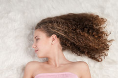 Girl with perfect curly hair lying on fur bed Stock Images
