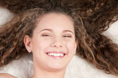Girl with perfect curly hair lying on fur bed Stock Image