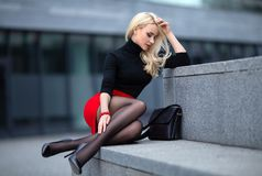 Girl with perfect legs in pantyhose at the city square