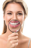 Girl with perfect teeth behind magnifying glass Royalty Free Stock Images