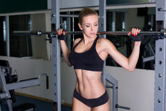 Girl performing barbell exercise Royalty Free Stock Image