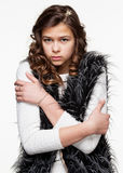Girl performing chill and discomfort. Gestures. Teenagers. Young girl in a light shirt and a fuzzy vest performing chill and discomfort, she freezes, isolated on Stock Photography