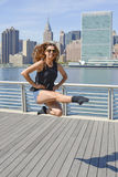 Girl performing Irish dance jump at Manhattan. Girl performing Irish dance birdie jump against Manhattan view Stock Images