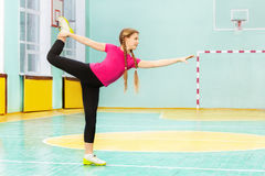 Girl performing swallow position in sports hall Stock Photography