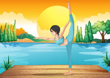 A girl performing yoga along the river in a sunset scenery Stock Image