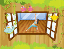 A girl performing yoga inside a house with birds at the window Royalty Free Stock Image