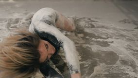 The girl performs a dance on lying on the floor and making circles in flour or white powder. A young girl in black stock video