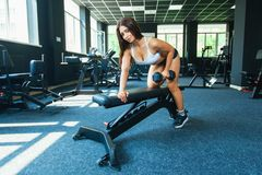 A girl performs a dumbbell with one hand in the slope using a bench. exercise on the broadest back muscles with. Dumbbells side view royalty free stock image