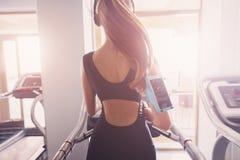A girl performs a god exercise on a treadmill. stock photos