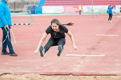 Girl performs a long jump. Orenburg, Russia - 24 April 2015: Girl performs a long jump on the sports contest students of institutions of secondary vocational Royalty Free Stock Images