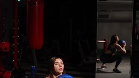 The girl performs squats with throwing the ball in her hands. Aerobic training. Young athletic woman squatting with a medicine ball at the wall stock video