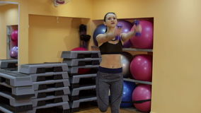Girl performs step cardio with dumbbells in a gym. stock footage