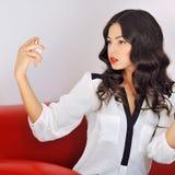 Girl with perfume. Young beautiful woman holding bottle of perfu Stock Image
